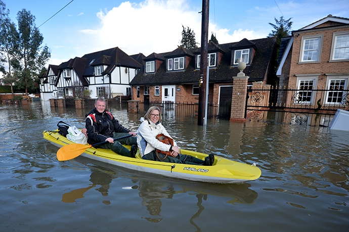 Residents paddle through floodwater in the village of Wraysbury in Berkshire, South East England, on February 10, 2014. (AFP Photo / Ben Stansall)