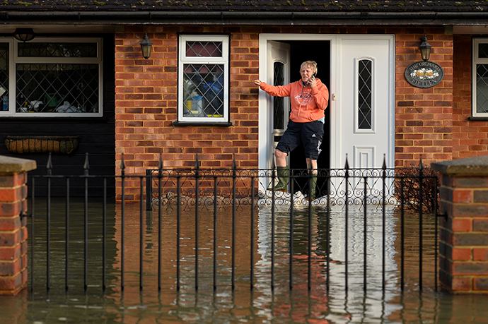 A residents stands at her front door in floodwater in the village of Wraysbury in Berkshire, South East England, on February 10, 2014. (AFP Photo / Ben Stansall)
