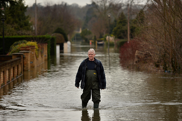 A resident walks through flood water in Wraysbury, Berkshire, on February 10, 2014. (AFP Photo / Ben Stansall)