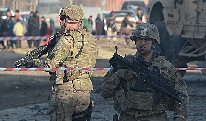 US soldiers, part of the NATO-led International Security Assistance Force (ISAF), stand guard at the site of a car bomb in the Pol-e-Charkhi area of Kabul on February 10, 2014. (AFP Photo / Shah Marai)