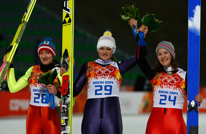 First placed Germany's Carina Vogt (C), second placed Austria's Daniela Iraschko-Stolz (L) and third placed France's Coline Mattel pose during the flower ceremony of the women's ski jumping individual normal hill event at the Sochi 2014 Winter Olympic Games, at the RusSki Gorki Jumping Centre, in Rosa Khutor February 11, 2014 (Reuters / Michael Dalder)