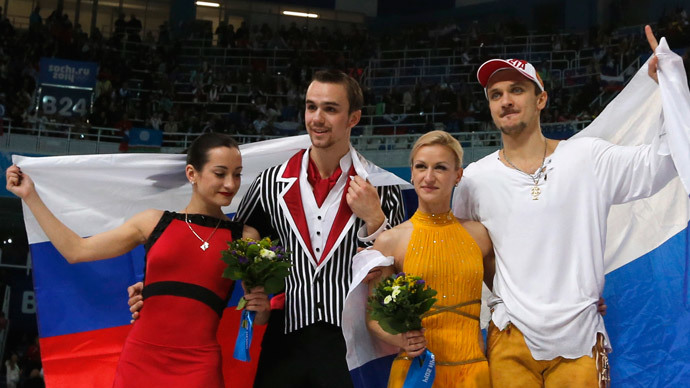 Second-placed Ksenia Stolbova (L) and Fedor Klimov (2nd L) of Russia pose with compatriots, first-placed Tatiana Volosozhar (2nd R) and Maxim Trankov, in front of the Russian national flag, after the figure skating pairs free skating at the Sochi 2014 Winter Olympics, February 12, 2014 (Reuters / Alexander Demianchuk)