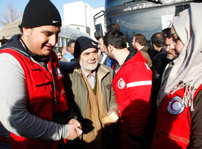 Members of the Syrian Arab Red Crescent assist a man evacuated from a besieged area of Homs, after his arrival to the area under government control February 7, 2014.(Reuters / Khaled al-Hariri )