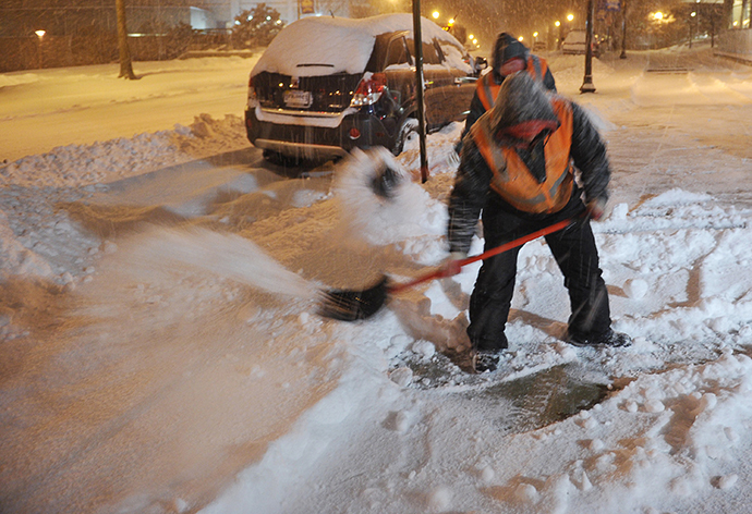 A worker clears snow from a sidewalk in Chevy Chase, Maryland, in the early hours of February 13, 2014. (AFP Photo / Mandel Ngan)