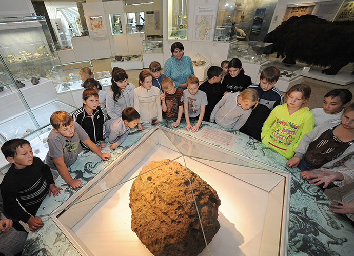 Children look at Chelyabinsk meteorite exhibited at Chelyabinsk Museum of Regional Studies. (RIA Novosti / Aleksandr Kondratuk)