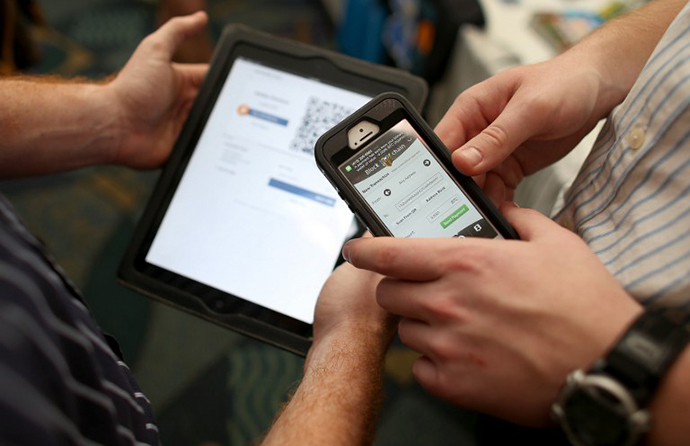 Eric Martindale (L) and John Dreyzehner from BitPay, the world leader in Bitcoin business solutions, demonstrate a transaction using an ipad to charge a customer who is using his phone to transfer Bitcoins for the purchase (AFP Photo / Joe Raedle)