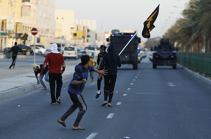 Anti-government protesters throw stones at riot police after the funeral procession for Asma Hussain, in the village of Jid Al Haj, west of Manama, February 12, 2014. (Reuters / Hamad I Mohammed)