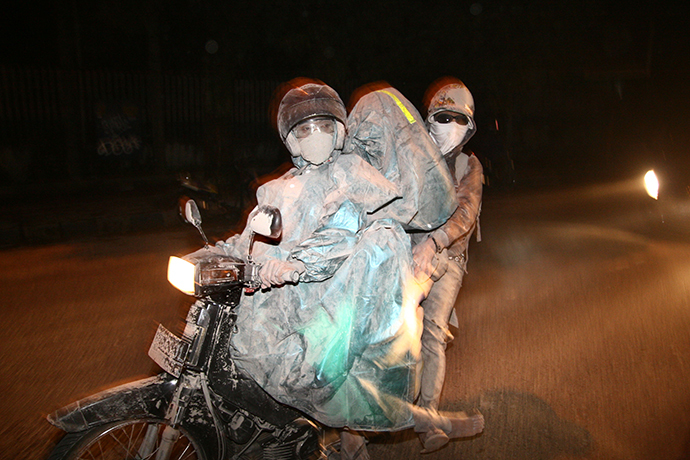 Residents evacuate to a safe place by riding a motorbike in Malang, East Java province, on February 14, 2014 moment after Mount Kelud erupted. (AFP Photo / Aman Rochman)
