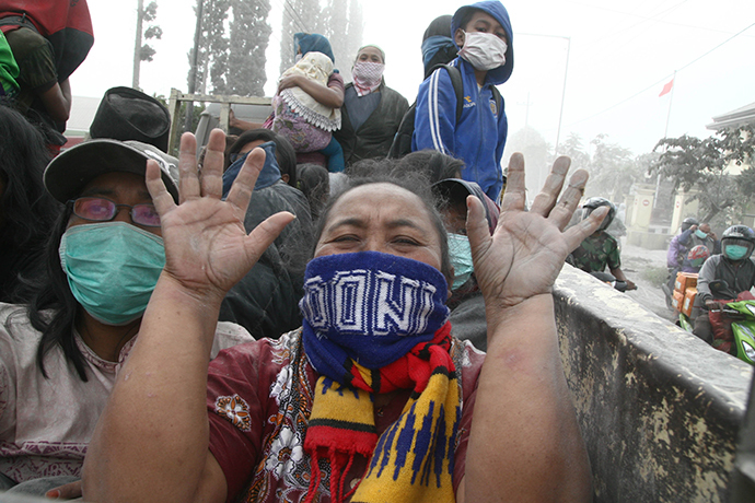 A woman gestures during the evacuation in Malang, East Java province, on February 14, 2014 moment after Mount Kelud eruption. (AFP Photo / Aman Rochman)