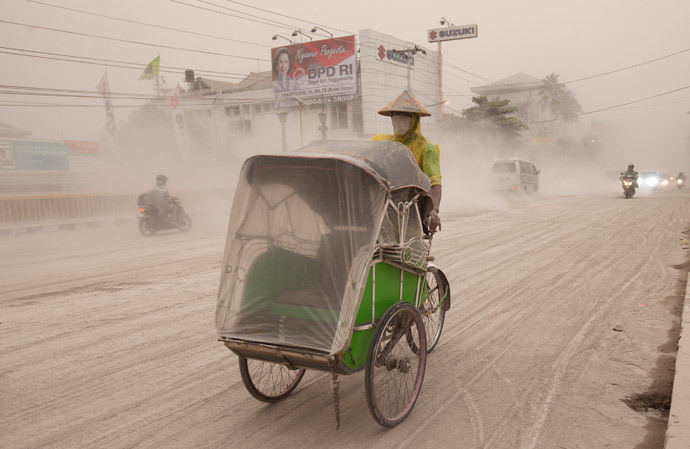 A man wears a mask as he rides a becak, a kind of rickshaw, on a road covered with from Mount Kelud, in Yogyakarta February 14, 2014. (Reuters / Dwi Oblo)