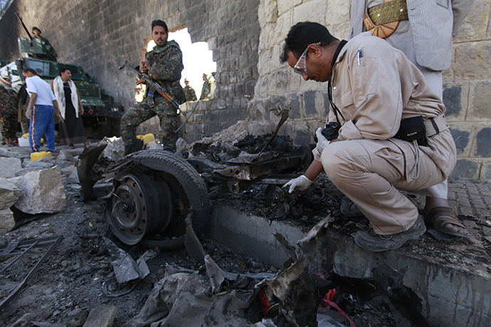 Investigators from the criminal investigation department (CID) examine the wreckage of a car after a bomb exploded outside the main wall outside the central prison in Sanaa February 14, 2014. (Reuters / Mohamed Al-Sayaghi)