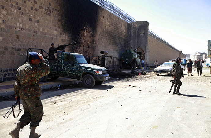 Policemen stand guard next to a wall of the central prison in Sanaa after a bomb exploded outside, February 14, 2014. (Reuters / Mohamed Al-Sayaghi)