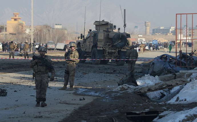 US soldiers, part of the NATO-led International Security Assistance Force (ISAF), stand near a damaged vehicle at the site of a car bomb in the Pol-e-Charkhi area of Kabul on February 10, 2014. (AFP Photo / Shah Marai)
