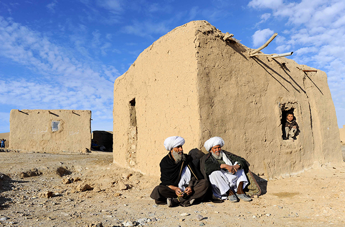 Afghan residents sit outside a hut on the outskirts of Herat on February 12, 2014. (AFP Photo / Aref Karimi)