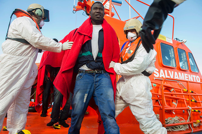 Members of the Spanish emergency services help a would-be immigrant to disembark a coastguard vessel at Tarifa's harbour after 17 would-be immigrants were rescued in the Straight of Gibraltar on November 25, 2013. (AFP Photo / Marcos Moreno)