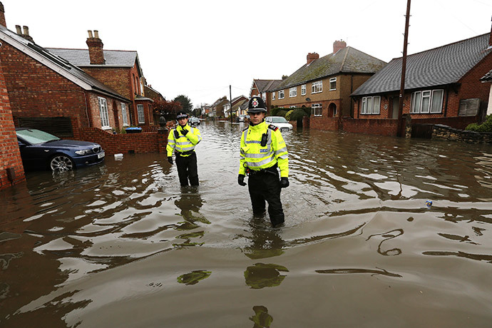 Police officers walk down a street in Egham after the River Thames burst its banks in southeast England February 14, 2014. (Reuters / Paul Hackett)