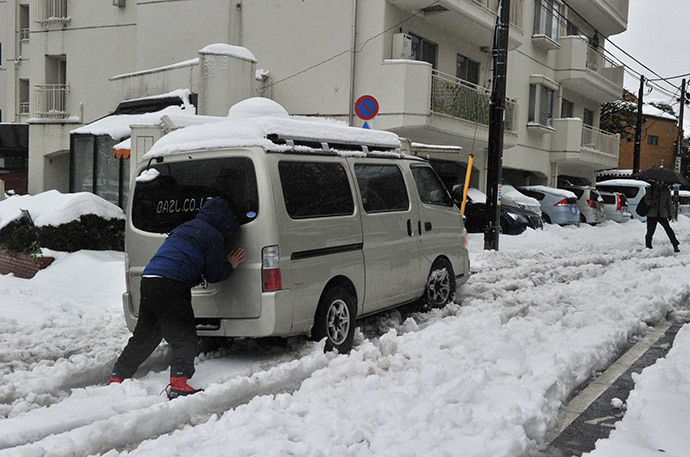A man pushes a vehicle after it lost traction and skidded on a snow covered road in Tokyo on February 15, 2014 as trafic is disrupted after a heavy snowfall. (AFP Photo / Yoshikazu Tsuno)