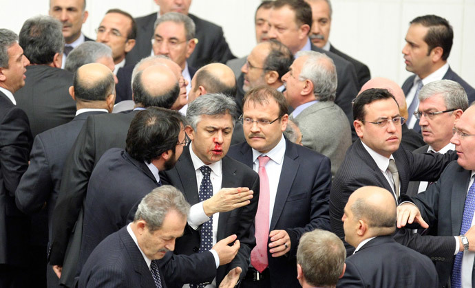 Member of parliament (MP) from the main opposition Republican People's Party (CHP) Ali Ihsan Kokturk's nose bleeds as MPs from the ruling AK Party (AKP) and CHP scuffle during a debate on a draft law which will give the government tighter control over the appointment of judges and prosecutors, at a parliamentary session in Ankara early February 15, 2014 (Reuters / Stringer)