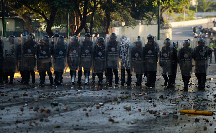 Riot policemen stand in line during clashes with anti-government students holding a protest in Caracas on February 15, 2014. ( AFP Photo / Juan Barreto )