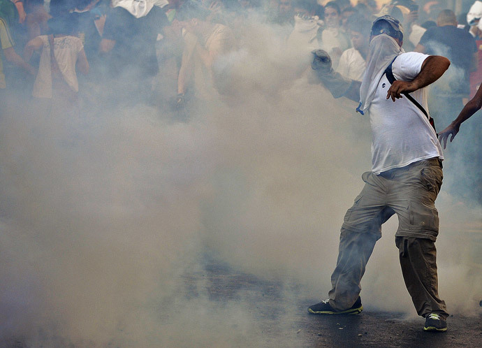Anti-government students throw stones to riot police during a protest, in Caracas on February 15, 2014. ( AFP Photo / Juan Barreto )
