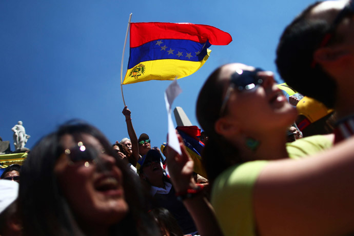 A Venezuelan opposition supporter waves a Venezuelan flag during a protest against Venezuelan President Nicolas Maduro's government at Angel de la Independencia monument in Mexico City, February 16, 2014.(Reuters / Edgard Garrido )