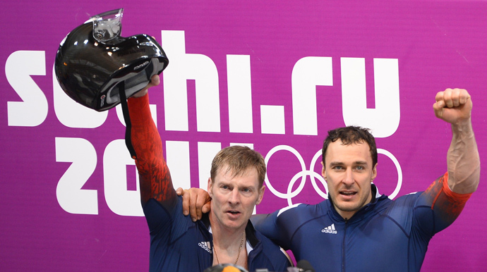 Russia-1 two-man bobsleigh pilot Alexander Zubkov (L) and brakeman Alexey Voevoda celebrate during the Bobsleigh Two-man Flower Ceremony at the Sliding Center Sanki during the Sochi Winter Olympics on February 17, 2014. (AFP Photo / Lionel Bonaventure)