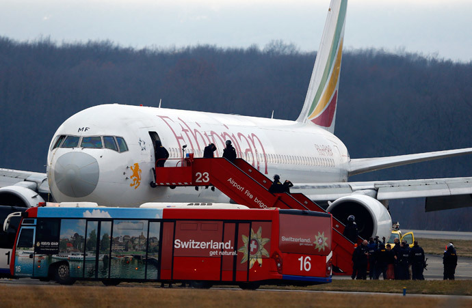 Passengers climb down an airplane ladder with their hands on their heads as police officers stand around hijacked Ethiopian Airlines flight ET 702 at Cointrin airport in Geneva February 17, 2014.(Reuters / Denis Balibouse)