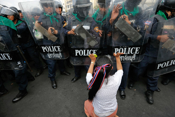 An anti-government protester pushes a line of policemen during clashes near the Government House in Bangkok February18, 2014.(Reuters / Damir Sagolj)