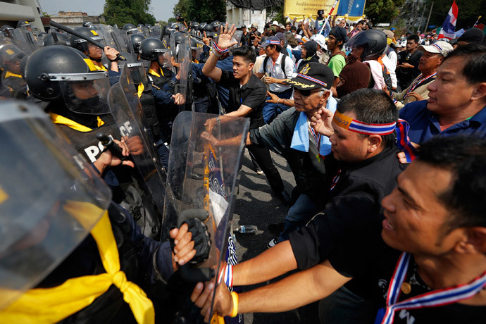 Policemen charge against anti-government protesters at one of their barricades near the Government House in Bangkok February 18, 2014. (Reuters / Damir Sagolj)