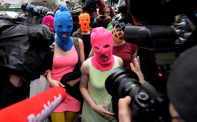Wearing masks members of Russian punk group Pussy Riot, Nadezhda Tolokonnikova (L) and Maria Alyokhina (R) speak to journalists while leaving the police station of Adler, near Sochi, on February 18, 2014 (AFP Photo / Andrej Isakovic)