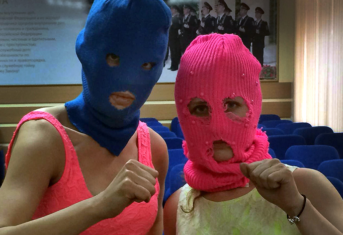 Wearing masks members of Russian punk group Pussy Riot, Nadezhda Tolokonnikova (L) and Maria Alyokhina (R), pose for a photo in a police station after their arrest in the Adler district of Sochi, on February 18, 2014.(AFP Photo / Evgeny Feldman)