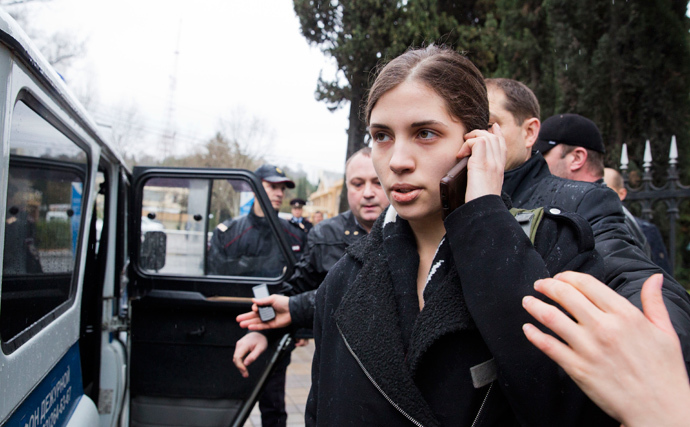 A members of Russian punk group Pussy Riot, Nadezhda Tolokonnikova, speaks by her cell phone, as she is escorted to a police car after being detained in the Adler district of Sochi, on February 18, 2014. (AFP Photo / Evgeny Feldman)