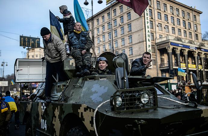 Mielenosoittajia seistä sotilaallinen panssaroitu ajoneuvo Kiovan keskustassa 26. helmikuuta 2014 (AFP Photo / Bulent Kilic)