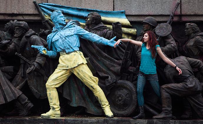 Nainen aiheuttaa kuvalle, jossa luvut neuvostoliittolaista sotilasta juuressa Neuvostoliiton armeijan muistomerkki, joista osa on maalattu värit Ukrainan lipun tuntematon henkilö, Sofiassa 23 helmikuu 2014 (Reuters / Pierre Marsaut )