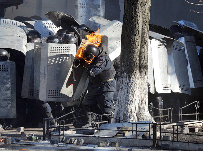 A photo taken on Febraury 18, 2014 shows a riot police whose helmet is burning, shielding himself during clashes with anti-government rioters in central Kiev. (AFP Photo / Genya Savilov)