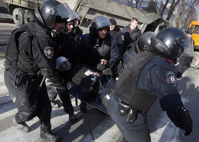 Policemen carry a colleague wounded during clashes in Kiev on February 18, 2014. (AFP Photo / Yury Kirnichny)