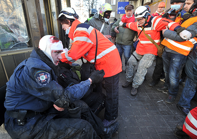 Red Cross workers give first aid to policemen wounded during clashes with anti-government rioter in Kiev on February 18, 2014. (AFP Photo / Genya Savilov)