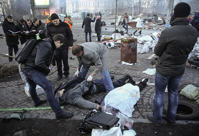 Forensic experts and police look at dead bodies lying on the ground after clashes between anti-government rioters and security officers, in central Kiev February 18, 2014. (Reuters / Konstantin Grishin)