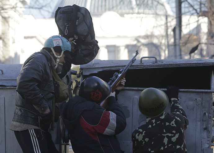 Rioters use a pneumatic gun as they take cover behind barricades during clashes with police in Kiev February 18, 2014. (Reuters / Konstantin Chernichkin)