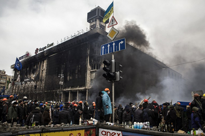 An anti-government rioters stand on February 19, 2014 outside the remains of the Trade Union building on Kiev's Independence Square during clashes with riot police. (AFP Photo / Sandro Maddalena)