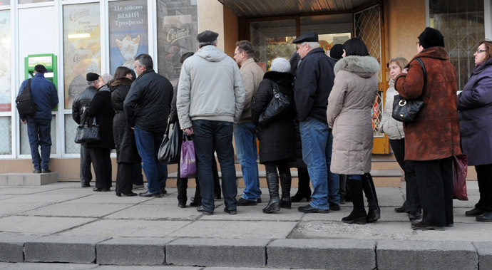 People stand in a queue to get their money from bank machine in the western Ukrainian city of Lviv on February 20, 2014, as a result of the financial panic caused with clashes between anti-government opposition and police in Kiev. (AFP Photo)