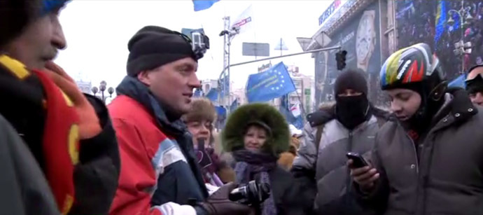 RT video still: Dmitry Zvershovsky (with camera) talks to protesters.
