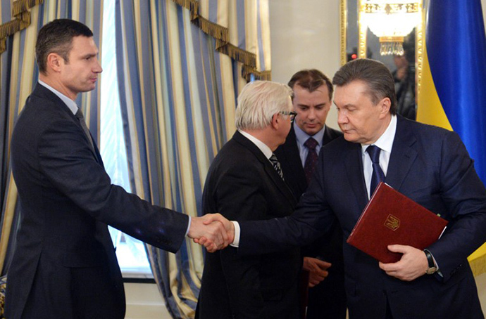 Head of Udar (Punch) party Vitali Klitschko (L) and Ukrainian President Viktor Yanukovych shake hands after signing an agreement in Kiev on February 21, 2014. (AFP Photo / Sergei Supinsky)