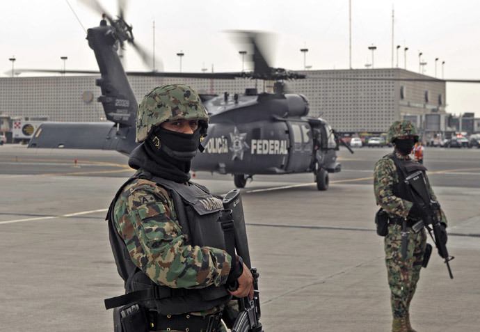 "Members of the Mexican Navy stand guard next to a helicopter transporting Mexican drug trafficker Joaquin Guzman Loera aka ""el Chapo Guzman"", on February 22, 2014 in Mexico City. (AFP Photo / Ronaldo Schemidt)"