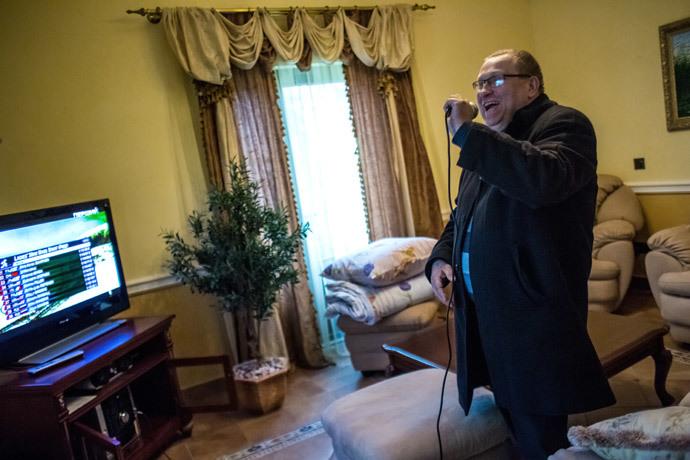 "A man sings karaoke in one of the rooms of the abandoned ""Mezhigorye"" residence of Ukrainian President Viktor Yanukovych near Kiev. (RIA Novosti / Andrey Stenin)"