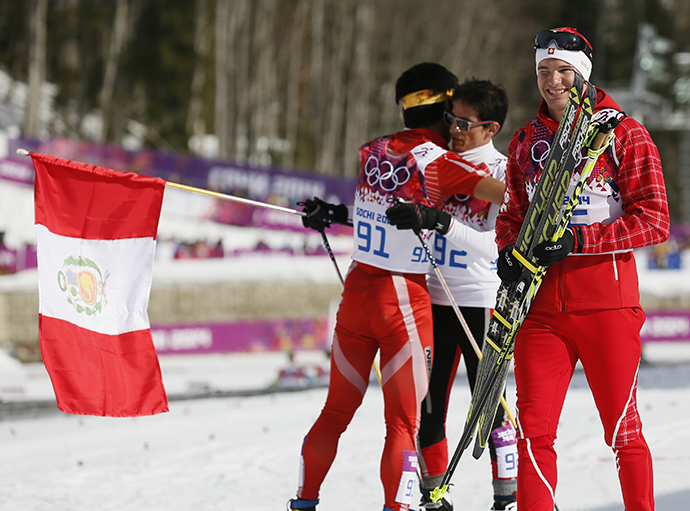 Switzerland's Dario Cologna (R) smiles as Peru's Roberto Carcelen and Nepal's Dachhiri Sherpa (L) embrace after crossing the finish line in the men's cross-country 15km classic event at the 2014 Sochi Winter Olympics February 14, 2014. (Reuters / Stefan Wermuth)