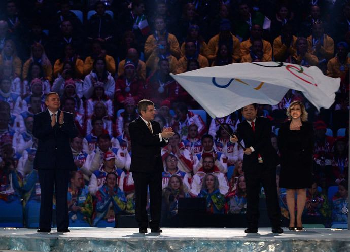 Mayor of Sochi Anatoliy Pakhomov (L) and International Olympic Committee (IOC) President Thomas Bach (C) applaud after handing over the Olympic flag to the Mayor of PyeongChang Lee Seok-rae during the Closing Ceremony of the Sochi Winter Olympics at the Fisht Olympic Stadium on February 23, 2014. (AFP Photo / Peter Parks)