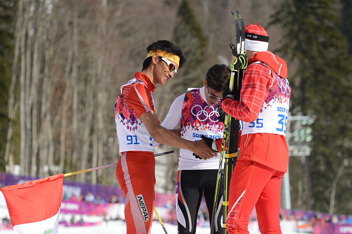 Peru's Roberto Carcelen (C) and by Nepal's Dachhiri Sherpa (L) are congratulated by gold winner Switzerland's Dario Cologna (R) after crossing the finish line in the Men's Cross-Country Skiing 15km Classic at the Laura Cross-Country Ski and Biathlon Center during the Sochi Winter Olympics on February 14, 2014. (AFP Photo / Kirill Kudryavtsev)