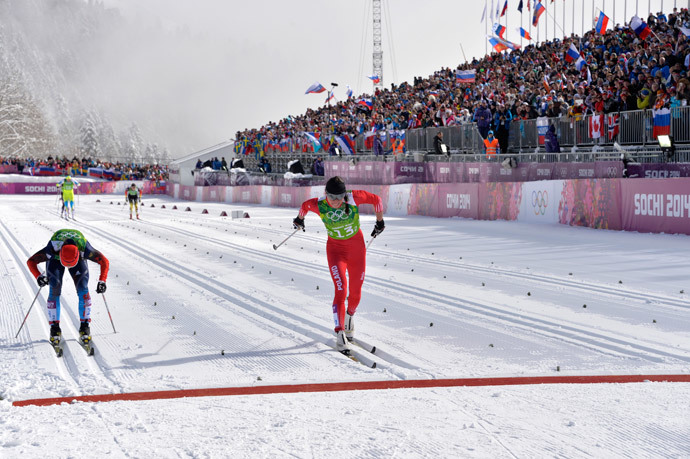 Poland's Justyna Kowalczyk (R) and Russia's Julia Ivanova reach the finish line as they compete in the Women's Cross-Country Skiing Team Sprint Classic Semifinals at the Laura Cross-Country Ski and Biathlon Center during the Sochi Winter Olympics on February 19, 2014 in Rosa Khutor near Sochi. (AFP Photo / Odd Andersen)