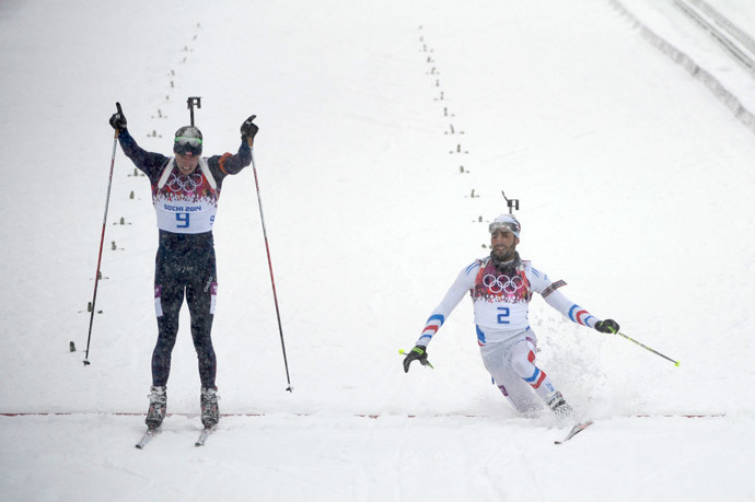 Gold medalist Norway's Emil Hegle Svendsen (9) and Silver medalist France's Martin Fourcade (2) cross the finish line in the Men's Biathlon 15 km Mass Start at the Laura Cross-Country Ski and Biathlon Center during the Sochi Winter Olympics on February 18, 2014, in Rosa Khutor, near Sochi. (AFP Photo / Pierre-Philippe Marcou)